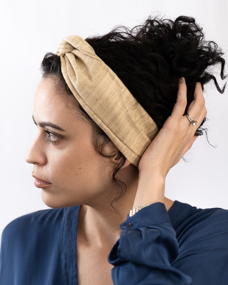 "Profile image of Latina millenial woman, wearing a blue shirtdress, with her hand touching her long dark curly hair which is styled in an up do topped with a beige colored turban style skinny headband: the ""Jute"" Khadi Mini Wire-Framed Headband."