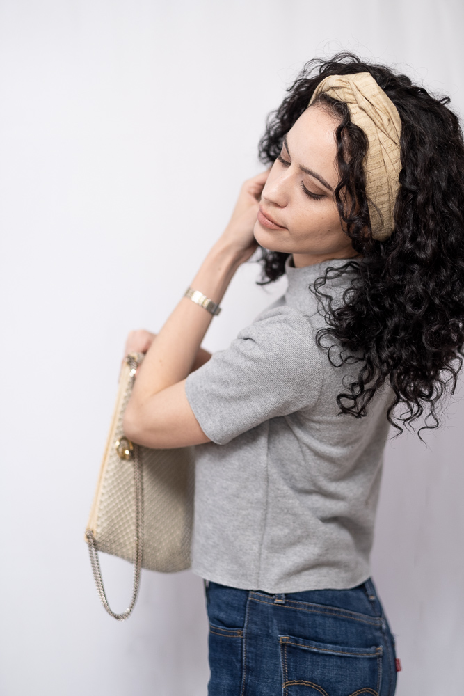 Image of millenial latina woman, brushing her hair back and holding a vintage purse, wearing a grey mock neck tee with dark blue jeans with black long curly hair wearing a thick, beige, turban style headband with her hair loose.