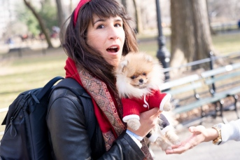 Happy woman wears red headband and holds teacup Pomeranian.