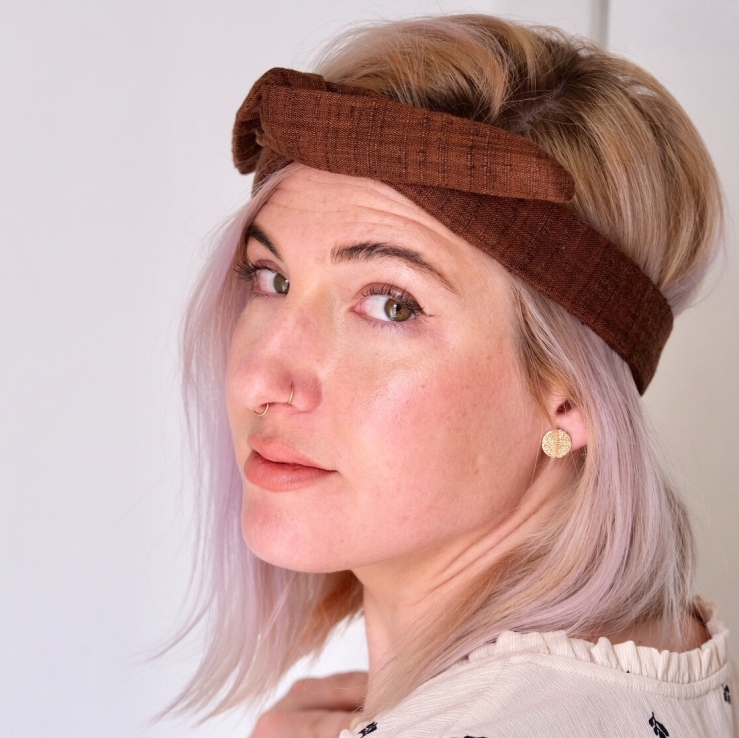 Beautiful millennial woman with blonde hair wears a brown headband.