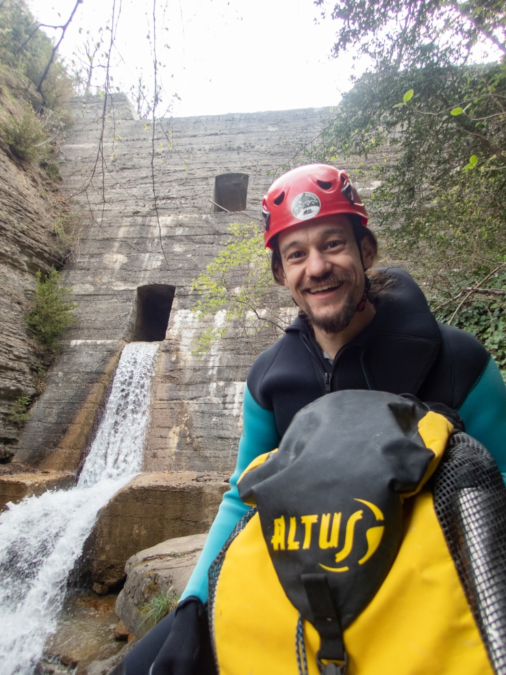 A man looks excited as he waits to rappel down a cliff during a canyoning excursion in Ainsa Spain.