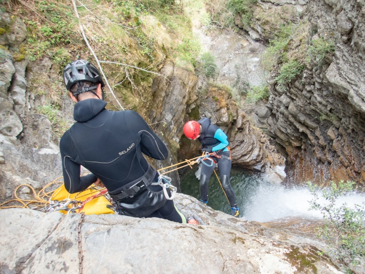 A woman starts to rappel down a cliff during a canyoning excursion in Ainsa Spain.