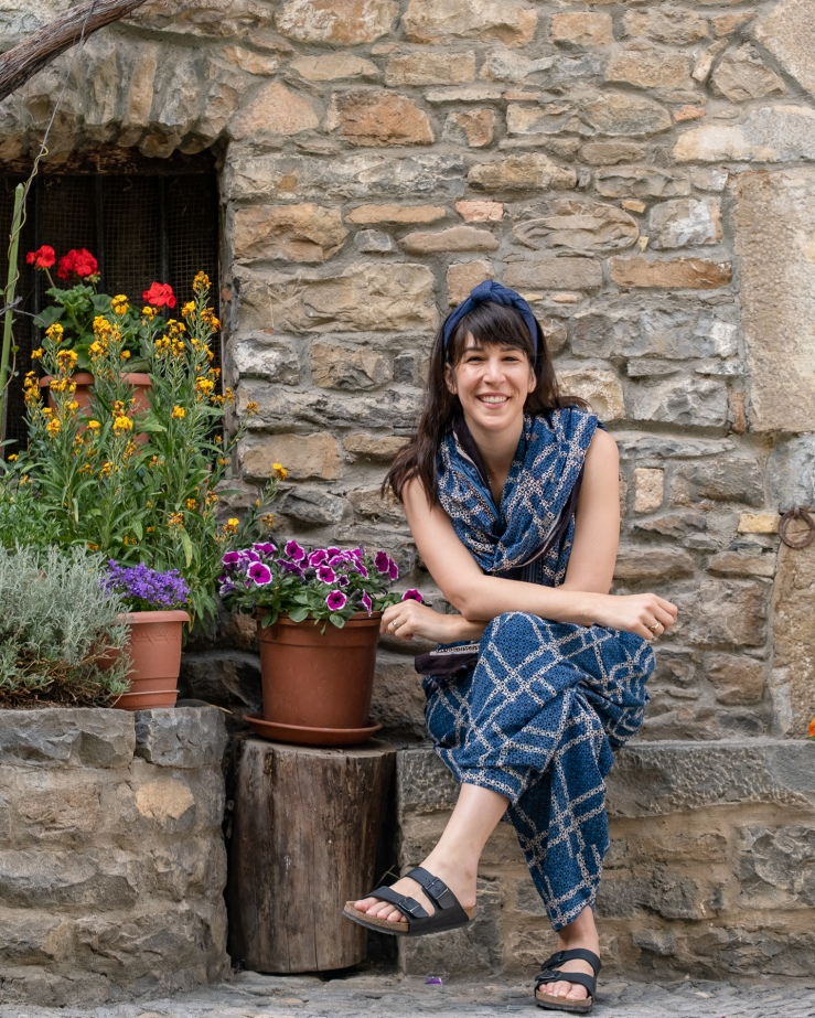 Woman with long brown hair sits next to flowers in Ainsa Spain and wears luxurious, handmade, blue khadi wire headband.