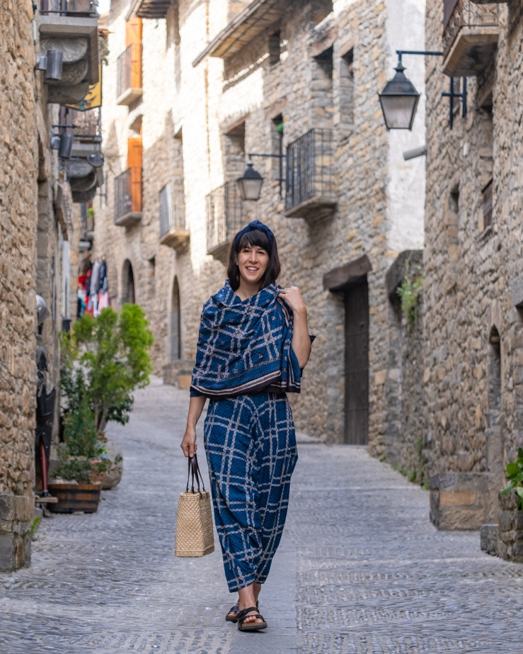 A woman wearing indigo textiles from India wanders the streets of Ainsa Spain wearing a luxurious, handmade blue khadi wire headband.