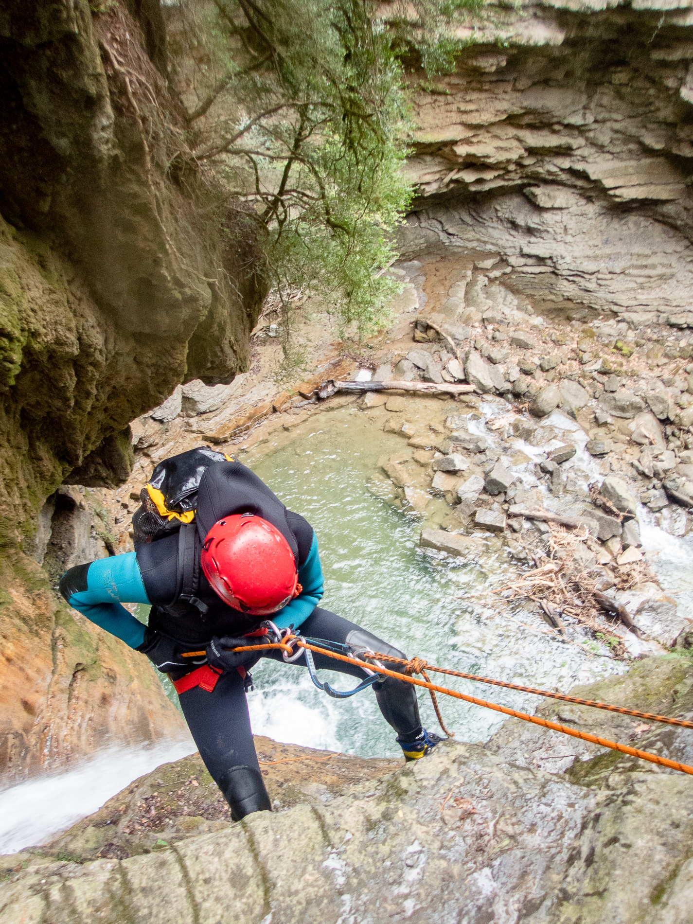 Person rappels down a cliff during a canyoning excursion in Ainsa Spain.