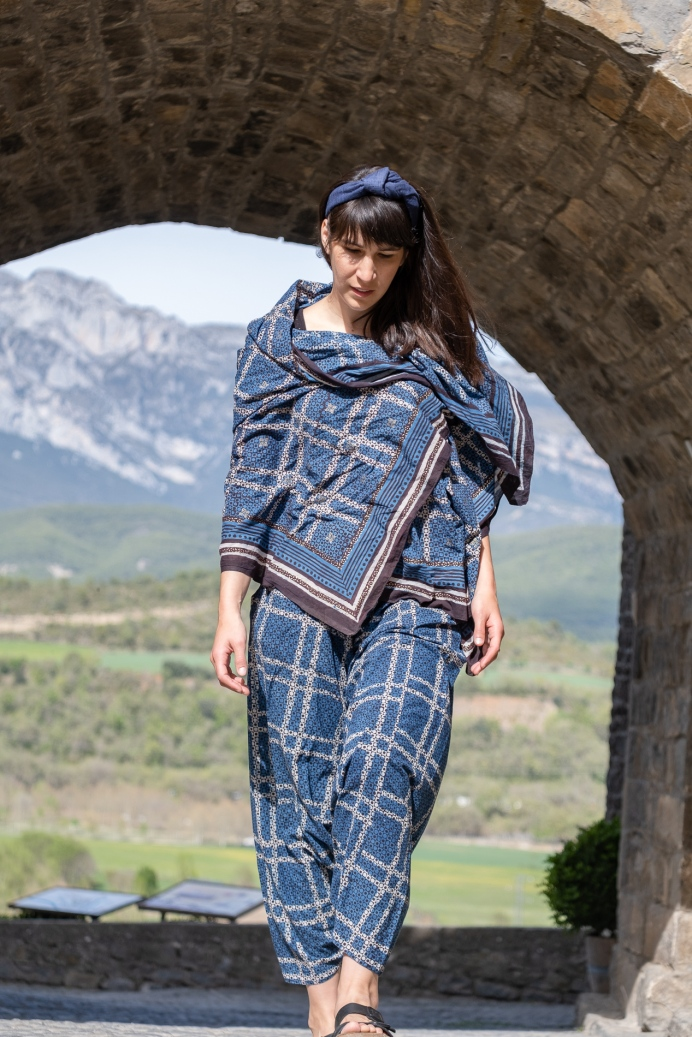 Woman in indigo textiles from India wears blue khadi wire headband during a trip to Ainsa Spain.
