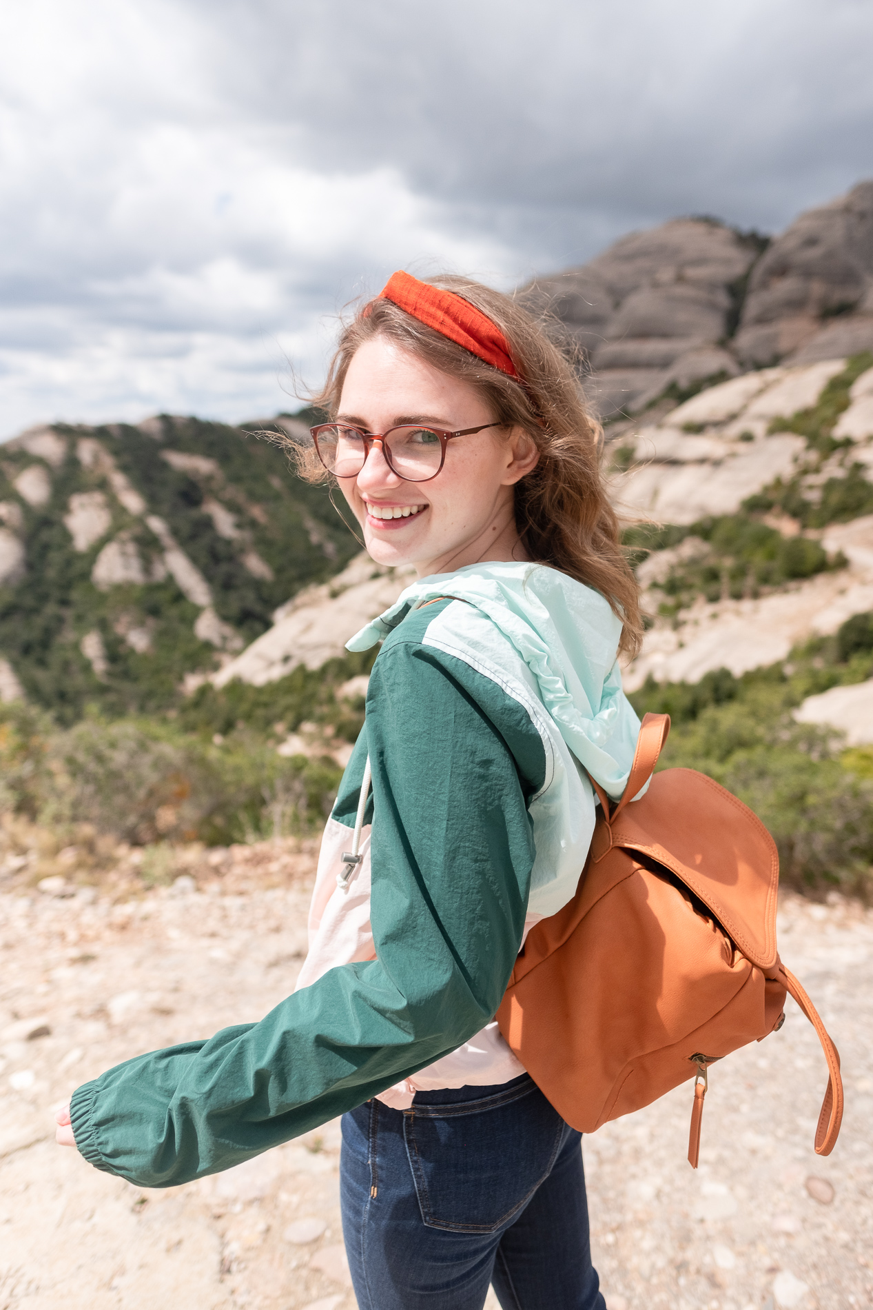 Woman with blonde hair and an orange headband and glasses smiles in the foreground, and we see the rocks of Montserrat in the background. She wears a colorblock parka and mini leather backpack.