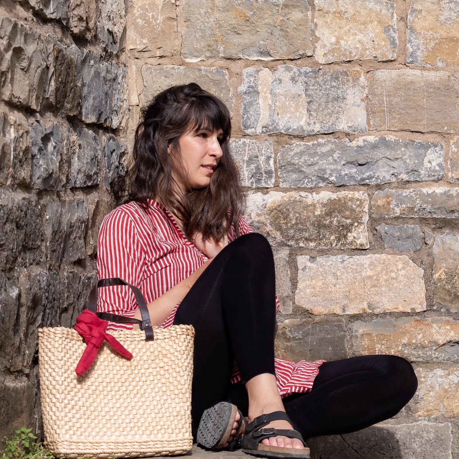 Woman with long wavy hair wears red and white striped tunic, Birkenstock sandals, and uses a red wire headband as a scarf to decorate her woven basket bag.