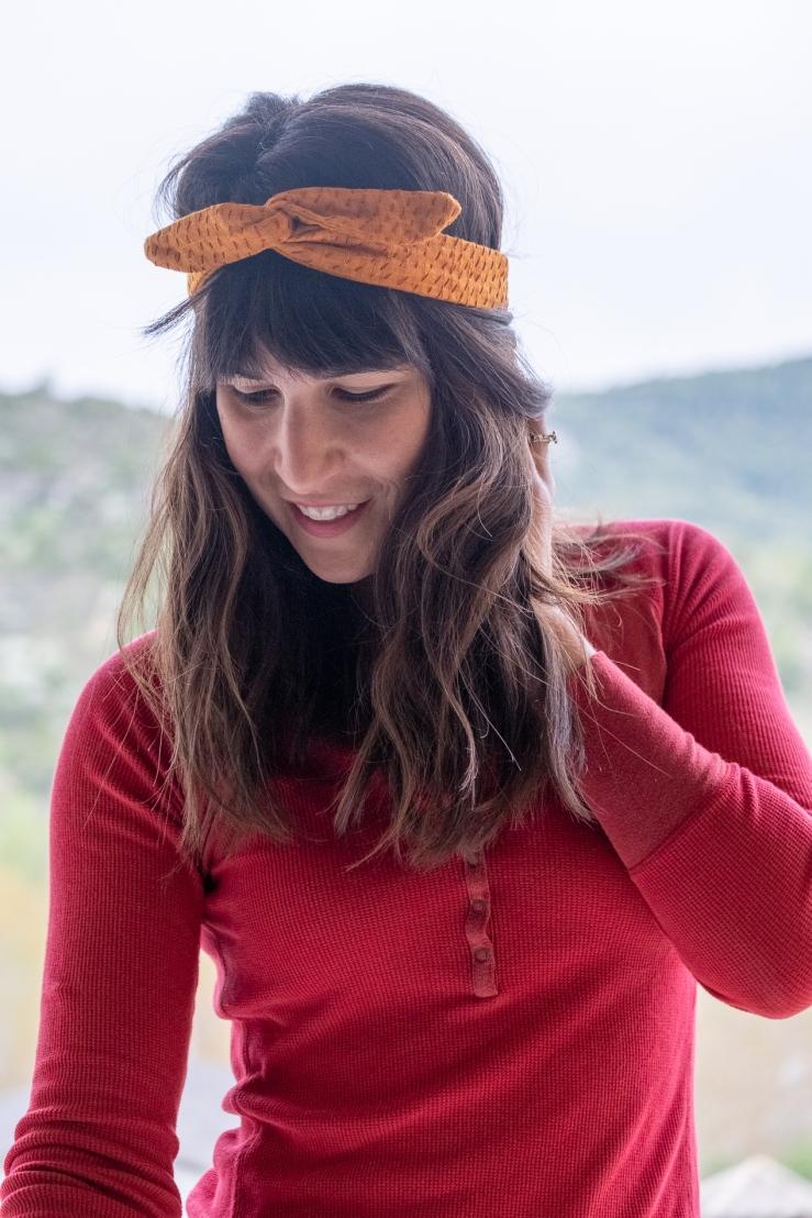 Woman wears luxurious handmade mustard yellow khadi wire headband embroidered with red thread.