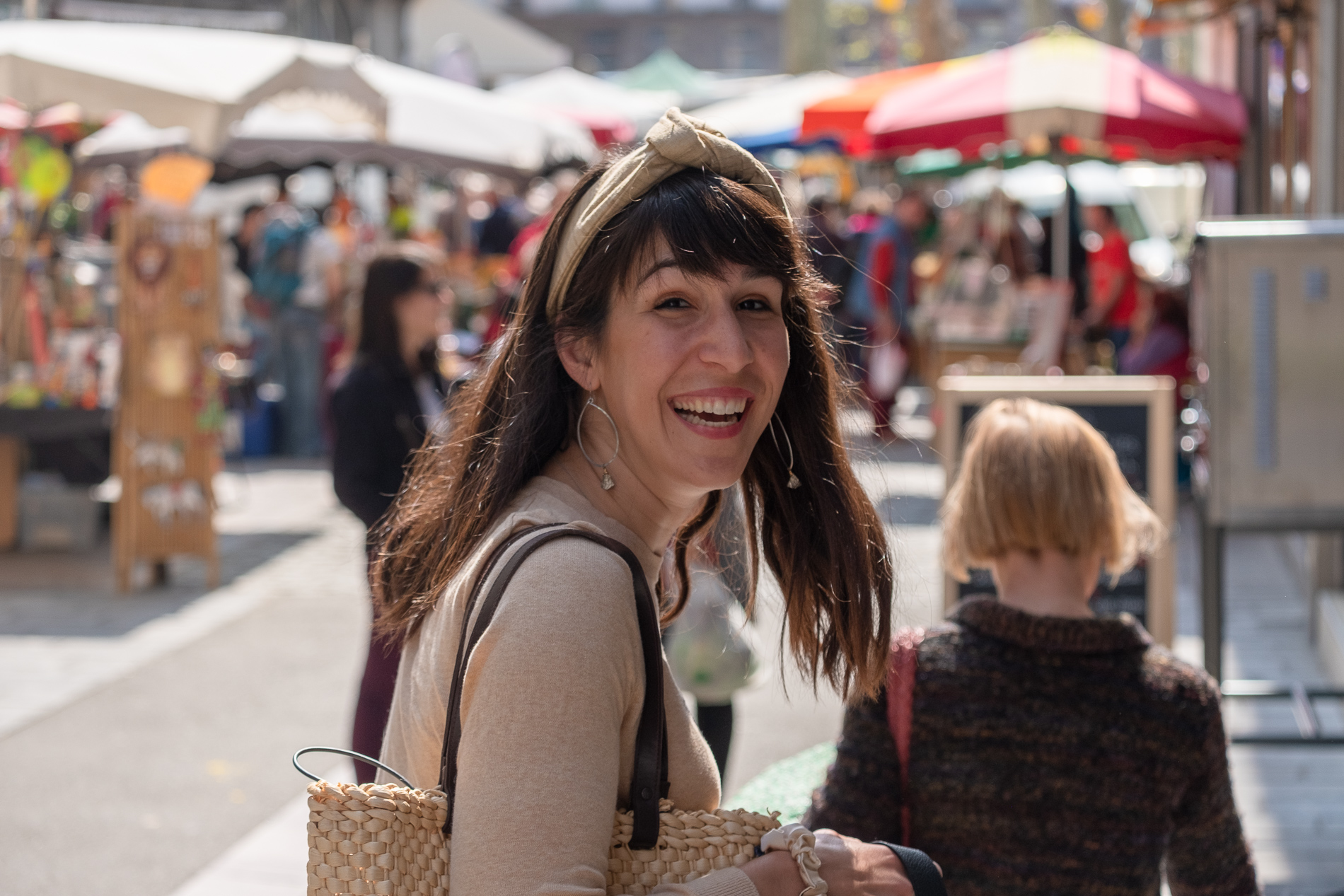 A woman wears a luxurious handmade beige khadi wire headband and looks overjoyed during a trip to Marche de St Girons France.