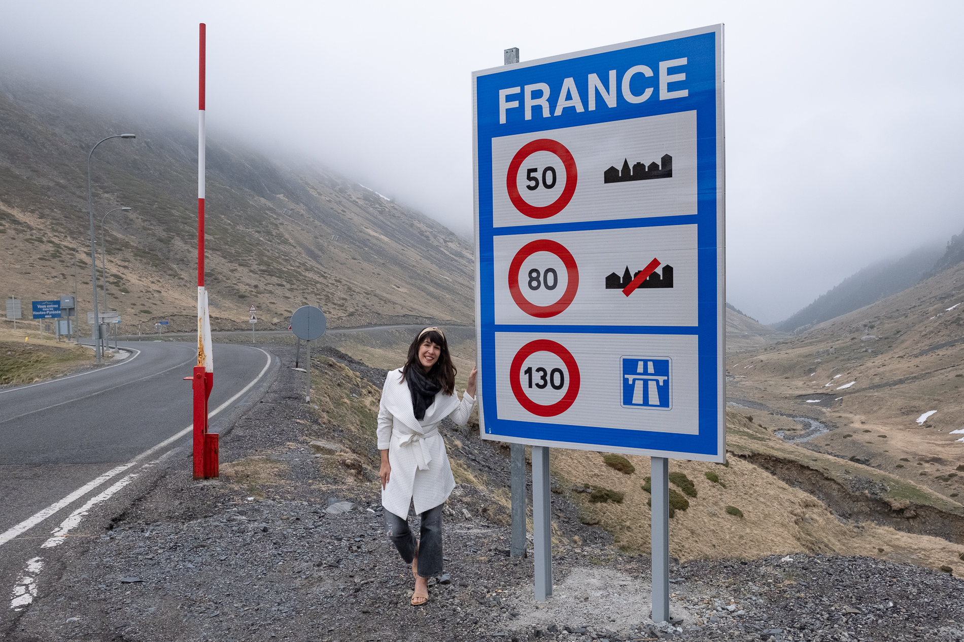"A French woman smiles as she stands next to sign that reads ""France"", at the end of the tunnel through the pyrenees from Spain to France. She wears a bright white coat like Meghan Markle and luxurious handmade beige khadi wire headband."