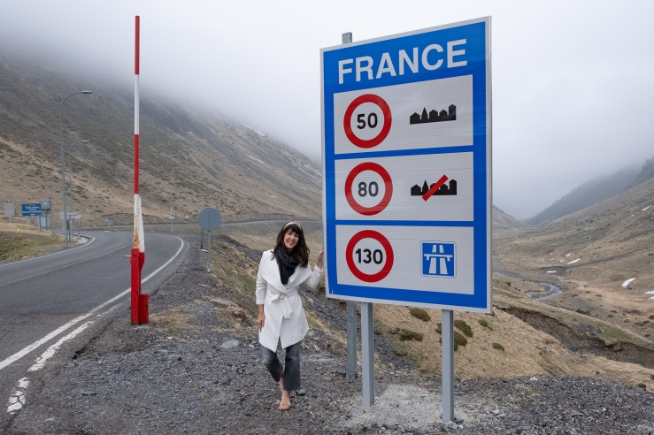 """A French woman smiles as she stands next to sign that reads """"France"""", at the end of the tunnel through the pyrenees from Spain to France. She wears a bright white coat like Meghan Markle and luxurious handmade beige khadi wire headband."""