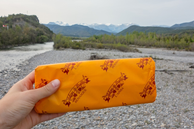 A person holds up a wrapped pastry in front of the Pyrenees mountains, view from Ainsa Spain.