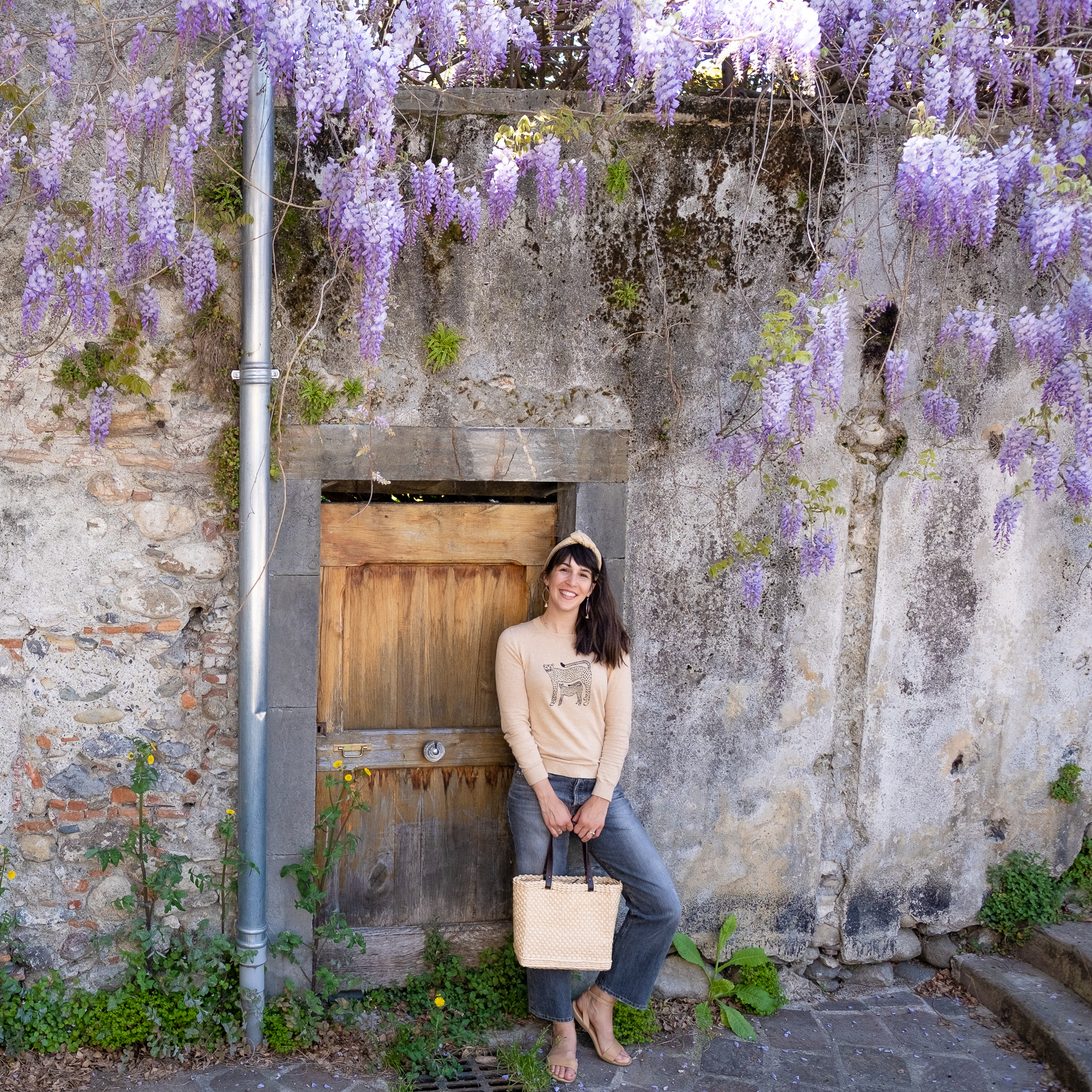 A woman wears a luxurious handmade beige khadi wire headband and stands under an arch of Wisteria in St Girons France.