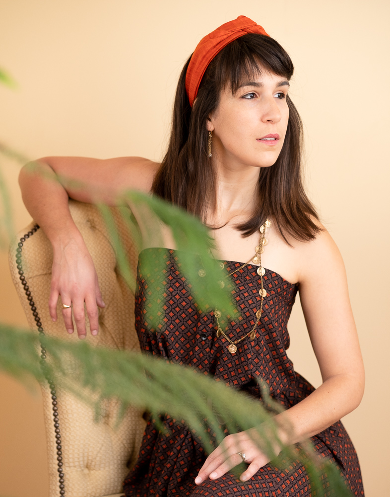 Woman with brown hair and orange headband wears a strapless dress and gold jewelry.  We see her through the branches of a tropical tree.