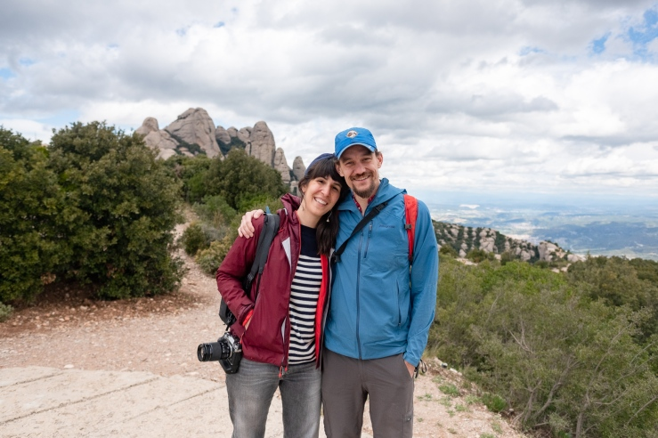 A happy couple stands on a mountain with views of Montserrat in the background. She wears a blue wire headband and carries a camera. He wears a blue hat.