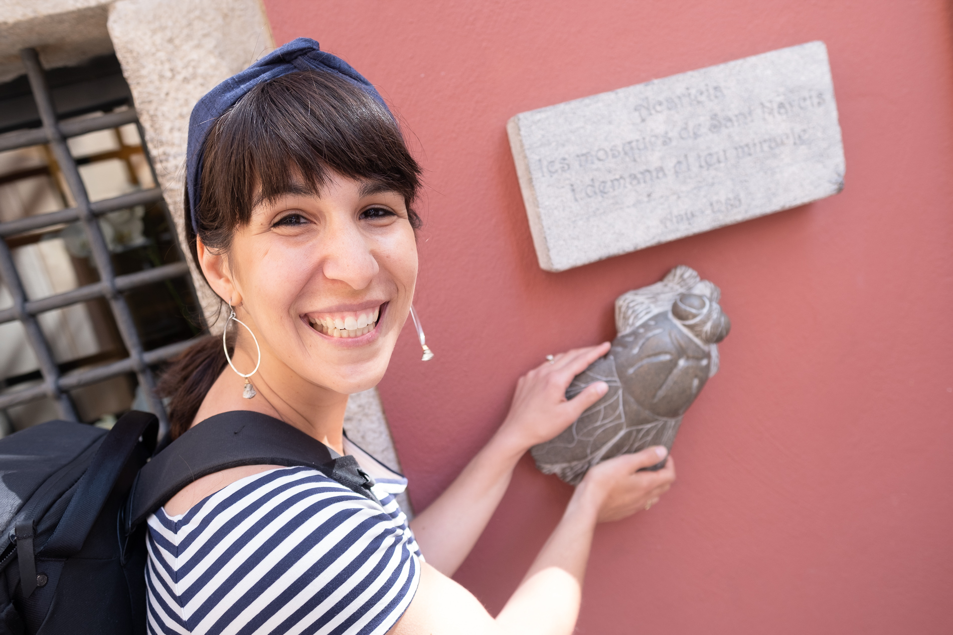 A woman smiles on a walking tour of Girona, as she touches a statue of a fly, and wears a blue wire headband.