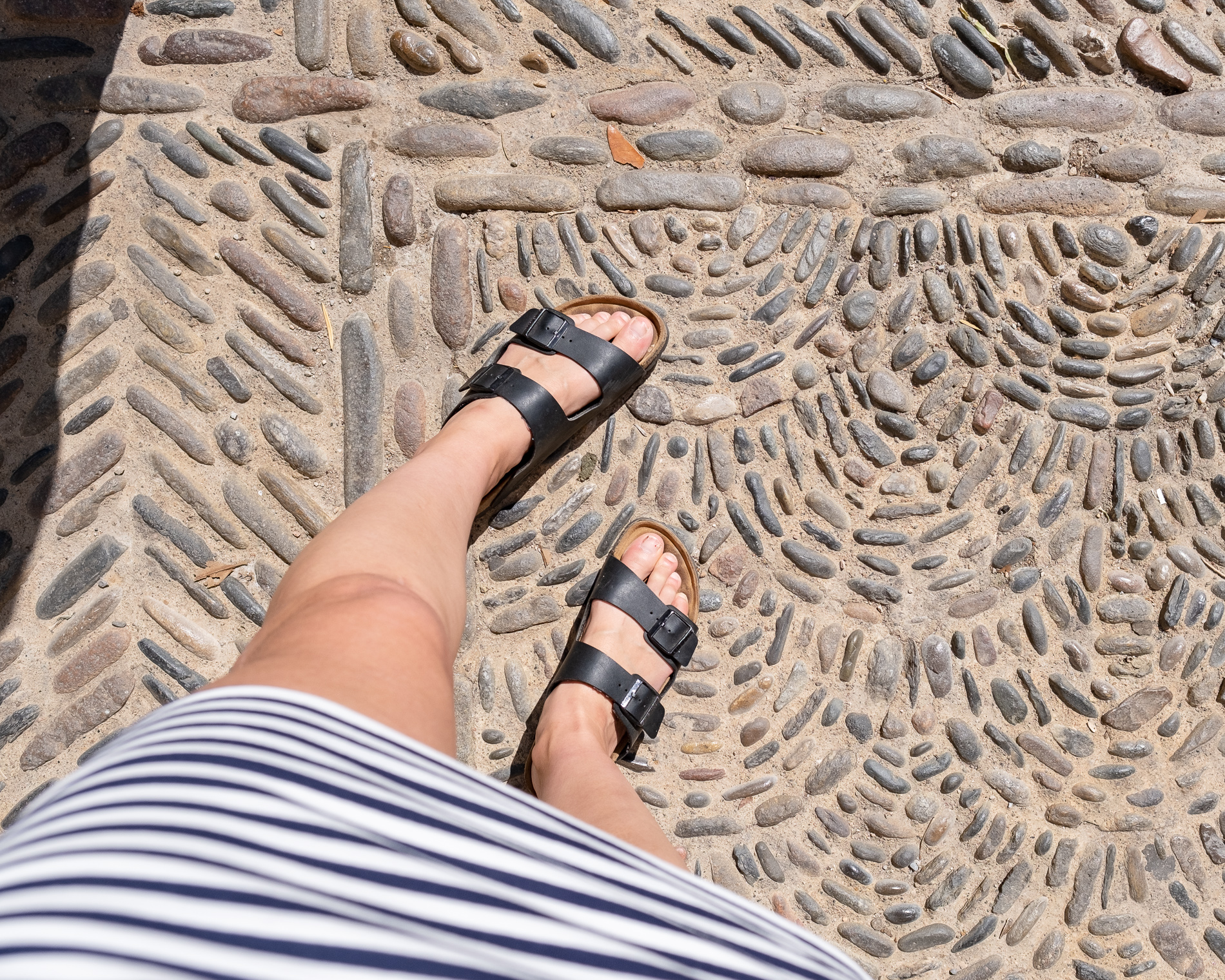 A woman's feet in Birkenstock sandals, on a beautifully cobbled street in Girona, Spain.