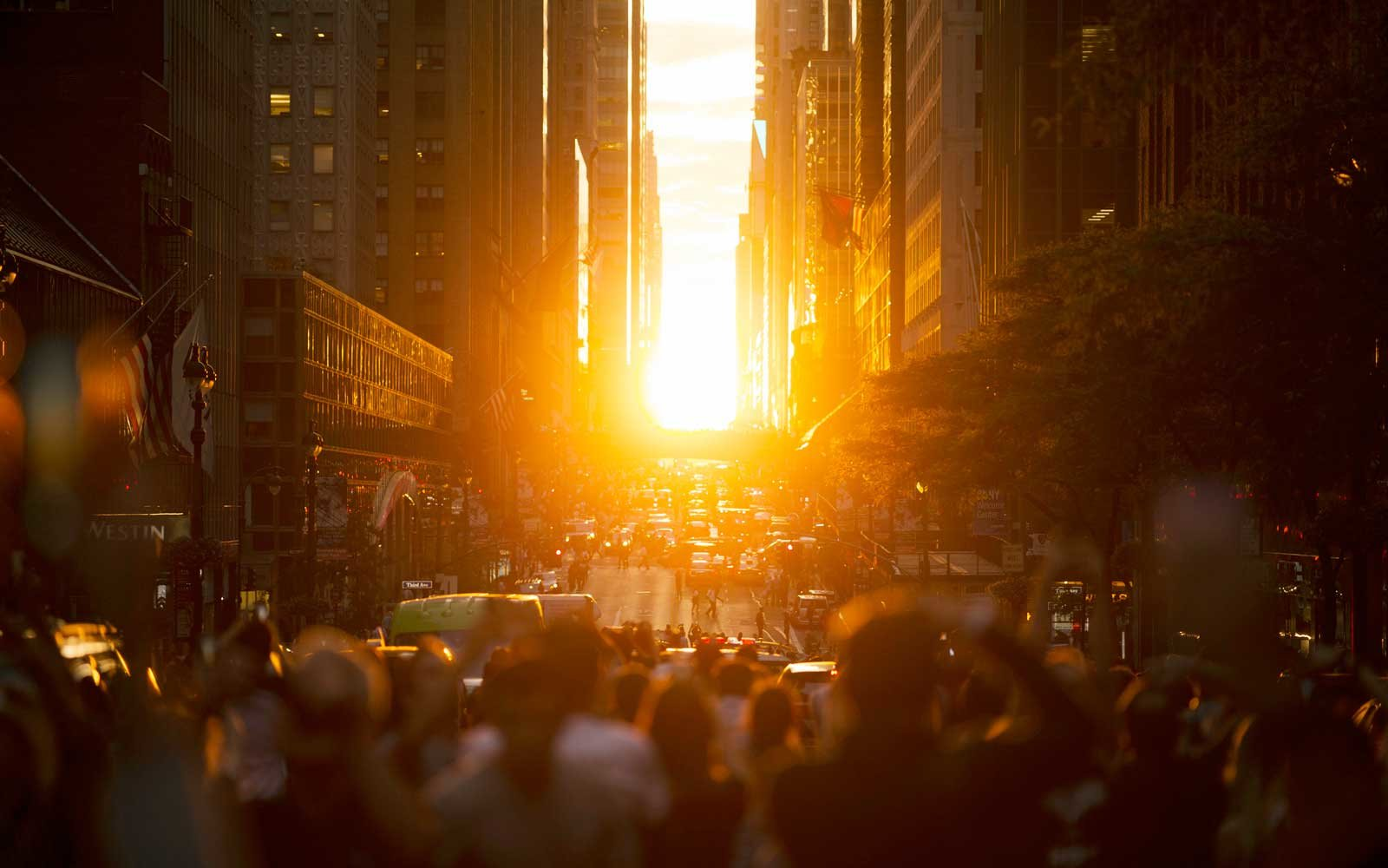 People observing the sunset during Manhattanhenge in New York City.
