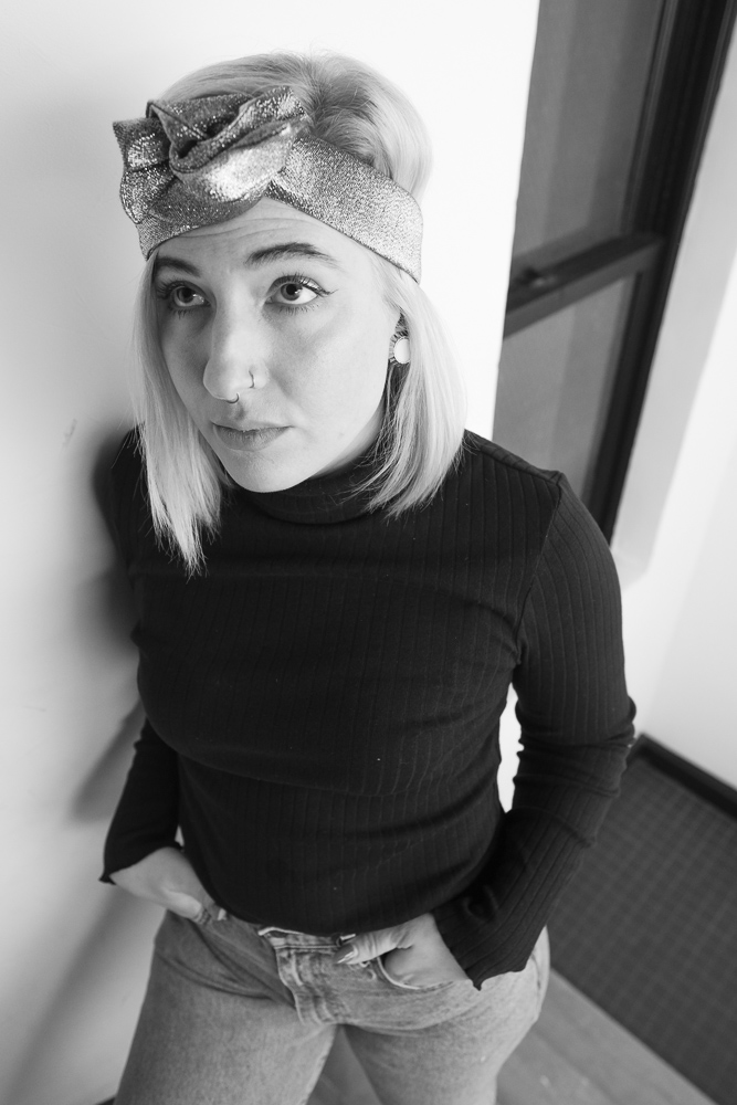 Beautiful woman with blonde hair wears a silver wire headband styled in a knot, with a turtleneck and jeans.