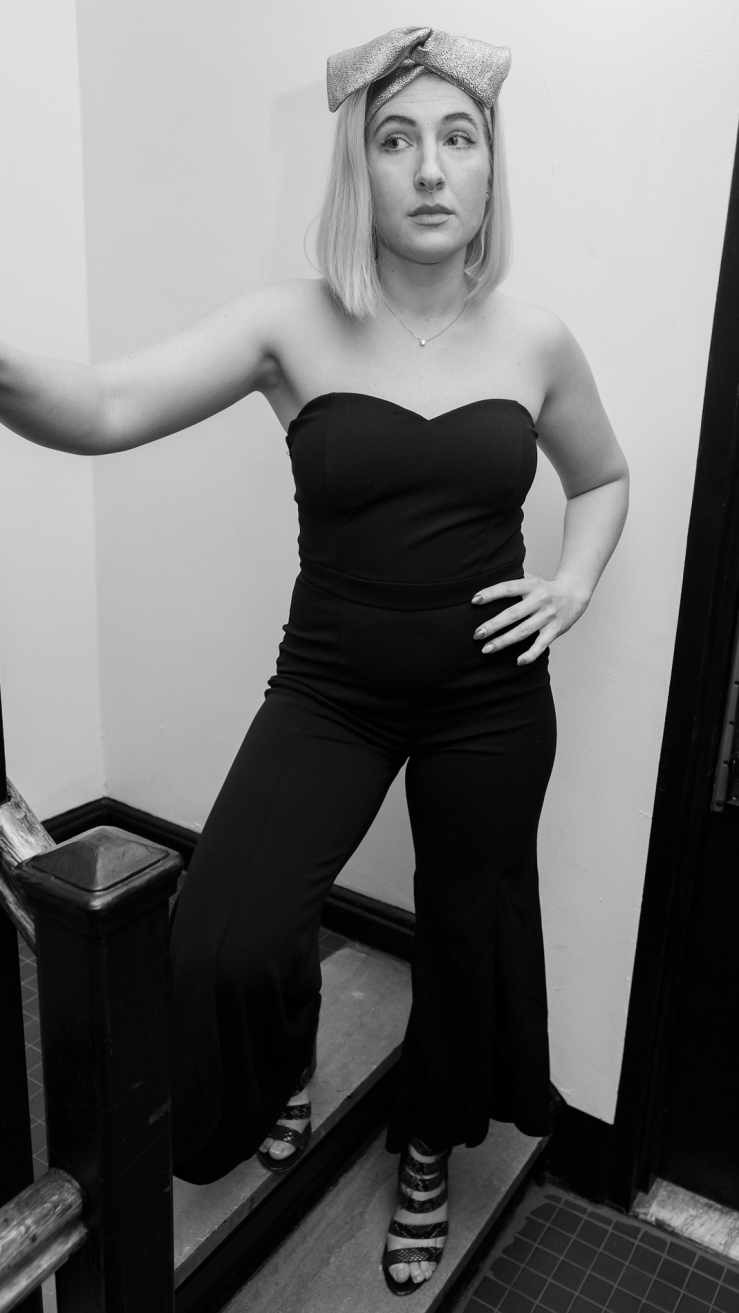 Full length photo of beautiful woman with blonde hair wears a silver wire headband styled in a dramatic bow, with a jumpsuit and scrappy heels.
