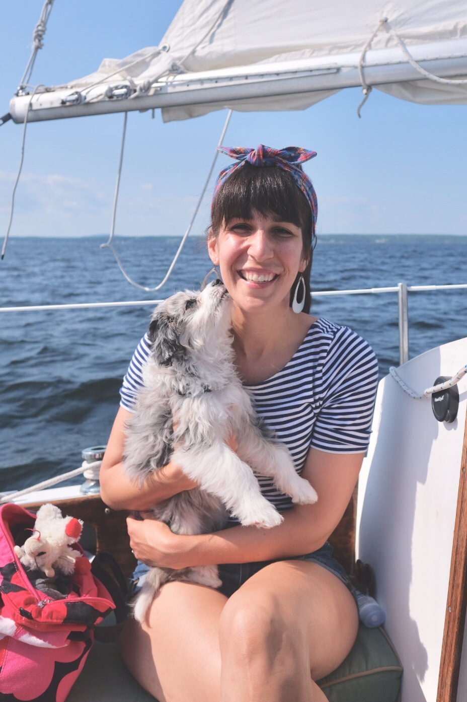 woman on a sailboat wearing headband with AussieDoodle puppy giving kisses.