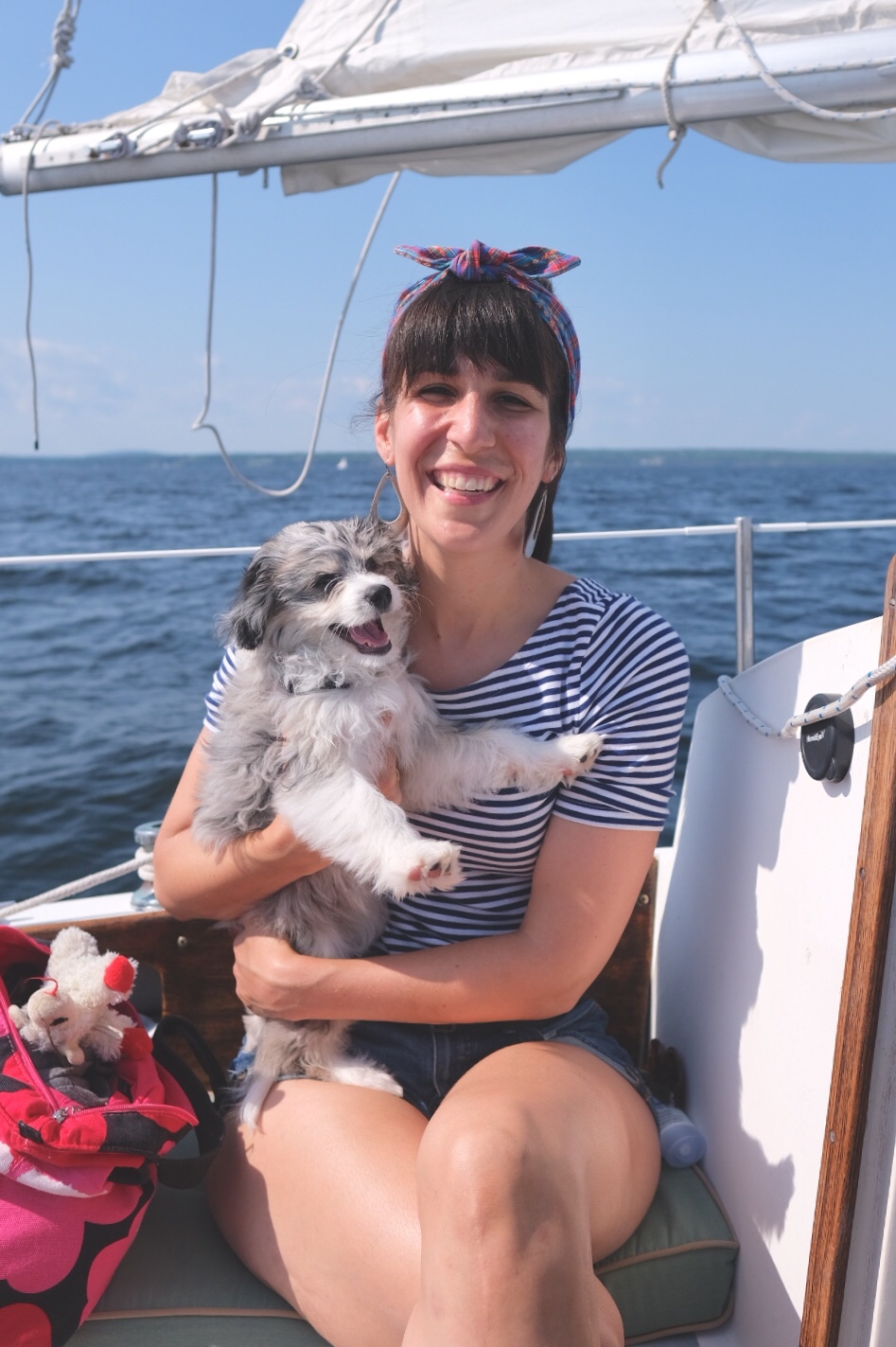 Smiling woman on a sailboat wearing headband with smiling AussieDoodle puppy.